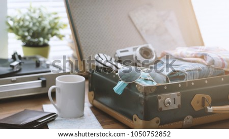 Traveler packing his luggage before leaving for a vacation: open vintage suitcase with clothes, camera and vintage record player, travel and retro revival concept
