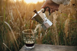 Traveler pouring fresh hot coffee from geyser coffee maker into glass cup in sunny warm light in rural countryside herbs. Atmospheric tranquil moment. Alternative coffee brewing in travel