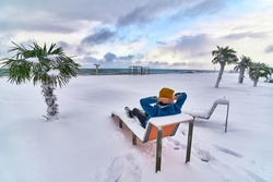 Traveler relaxing on a deck chair among evergreen tropical palm trees covered white snow standing in snowdrifts. Cold unusual weather in tropic