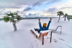 Traveler resting and relaxing on a deck chair among evergreen tropical palm trees covered white snow standing in snowdrifts. Cold unusual weather in tropic
