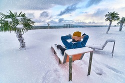 Traveler resting on a deck chair among evergreen tropical palm trees covered white snow standing in snowdrifts in a blizzard. Cold unusual weather in tropic