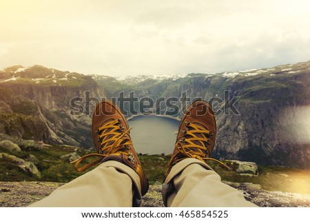 Shutterstock Traveler resting on a mountain plateau. POV view, legs close up on the background of mountain landscape