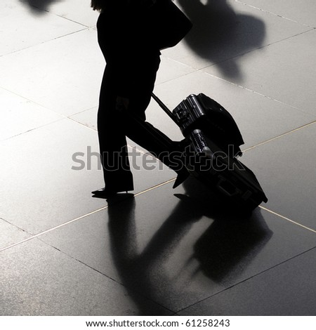 Traveler silhouette of business woman at airport walking with suitcases