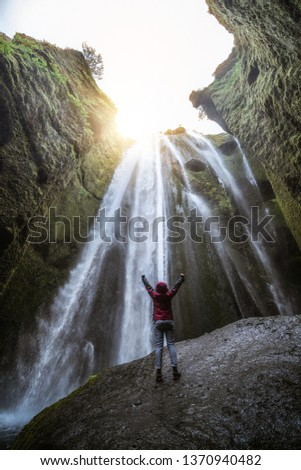 Traveler stunned by Gljufrabui waterfall cascade in Iceland. Located at scenic Seljalandsfoss waterfall South of Iceland, Europe. It is top beautiful destination of popular tourist travel attraction.