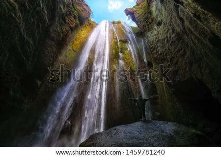 Traveler stunned by Gljufrabui waterfall cascade in Iceland. Location: Gljufrabui waterfall, part of the river Seljalandsa, Iceland, Europe