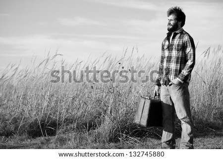 Traveler - This is a black and white image of a scruffy traveler holding a suitcase and looking ahead.