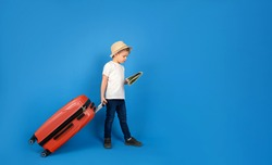 Traveler tourist child in casual clothes hat with suitcase map isolated on blue background. Passenger traveling abroad to travel on weekends getaway. Air flight journey concept.