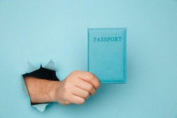 Traveler tourist man hand hold passport from a torn hole in blue paper