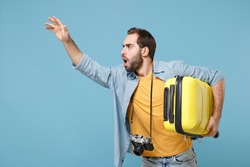 Traveler tourist man in yellow clothes with photo camera isolated on blue background. Male passenger travele abroad on weekends. Air flight journey. Hold suitcase waving hand for greeting, catch taxi