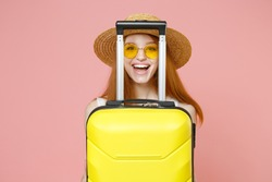 Traveler tourist smiling hapy ginger woman 20s in straw hat glasses hiding with suitcase valise isolated on pastel pink background Passenger travel abroad weekends getaway Air flight journey concept