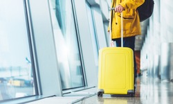 traveler tourist with yellow suitcase backpack at airport on background large window blue sky, man in bright jacket wait in hall of airport lobby terminal, vacation trip concept, empty space mockup