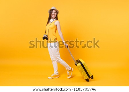 Traveler tourist woman in summer casual clothes, hat with headphones on neck isolated on yellow orange background. Passenger traveling abroad to travel on weekends getaway. Air flight journey concept #1185705946