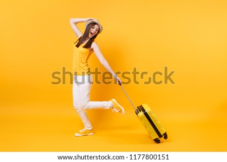 Traveler tourist woman in summer casual clothes, hat with suitcase isolated on yellow orange background. Female passenger traveling abroad to travel on weekends getaway. Air flight journey concept