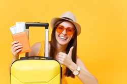 Traveler tourist woman in summer casual clothes, hat with suitcase showing thumb up isolated on yellow background. Passenger traveling abroad to travel on weekends getaway. Air flight journey concept