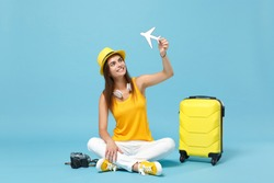 Traveler tourist woman in yellow casual clothes hat with suitcase photo camera isolated on blue background. Female passenger traveling abroad to travel on weekends getaway. Air flight journey concept