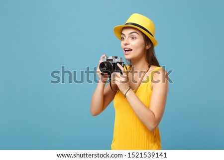 Traveler tourist woman in yellow summer casual clothes, hat with photo camera isolated on blue background. Female passenger traveling abroad to travel on weekends getaway. Air flight journey concept