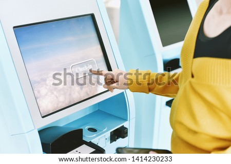 Traveler using a self check-in machine kiosk service at airport, Close up of finger point on display, Technology and smart application to confirm flight booking details, Travel concept. #1414230233