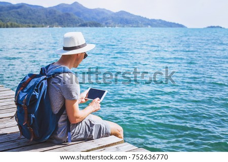 traveler using digital tablet computer while sitting on wooden pier, travel app online, man backpacker with wireless device #752636770