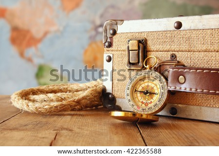 traveler vintage luggage and compass on wooden table. explorer and adventure concept