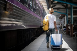 Traveler walking and waits train at train station for travel in summer. Travel concept.