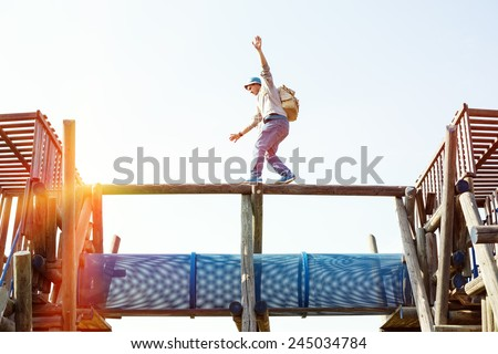 traveler walking balance over top of wooden construction with blue pipe
