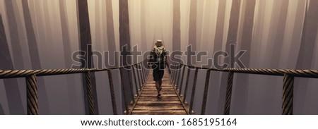 Traveler walking on bridge suspension over the misty forrest . This is a 3d render illustration . stock photo