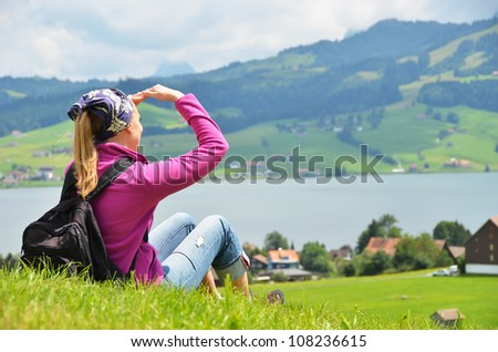 Traveler with a backpack on the hill - stock photo