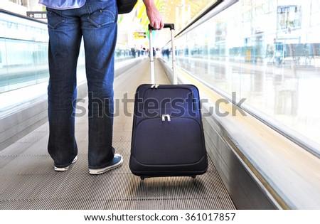 Traveler with a bag on the speedwalk #361017857