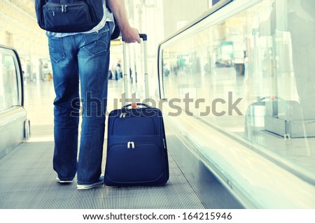 Traveler with a suitcase on the speedwalk  - stock photo