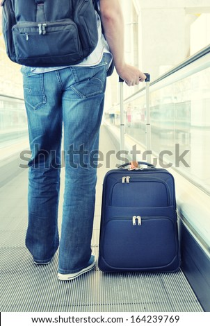 Traveler with a suitcase on the speedwalk  #164239769