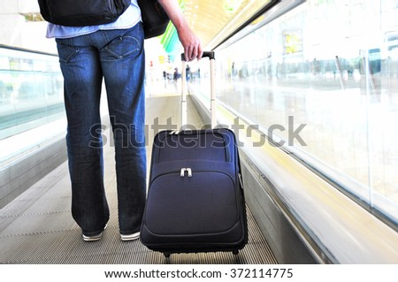 Traveler with a suitcase on the speedwalk #372114775