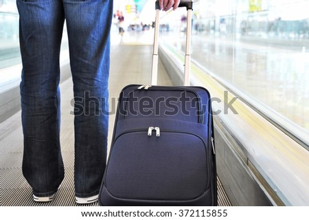 Traveler with a suitcase on the speedwalk #372115855