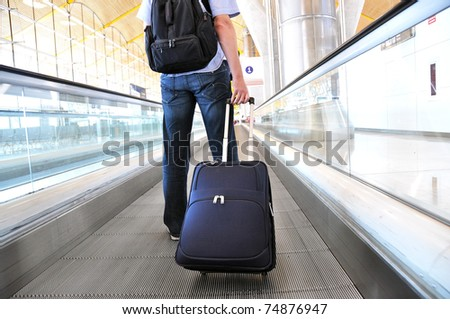 Traveler with a suitcase on the speedwalk #74876947
