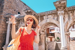 traveler with a toy plane on the background of the archaeological monument - the gate of the Emperor Hadrian in the old city of Antalya. Concept of air tickets and airlines in Turkey