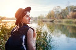 Traveler with backpack relaxing by autumn river at sunset. Young woman enjoys fall weather and landscape