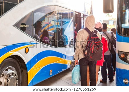 Traveler with backpack stand in queue line waiting to get in bus at bus station in Bangkok, Thailand.