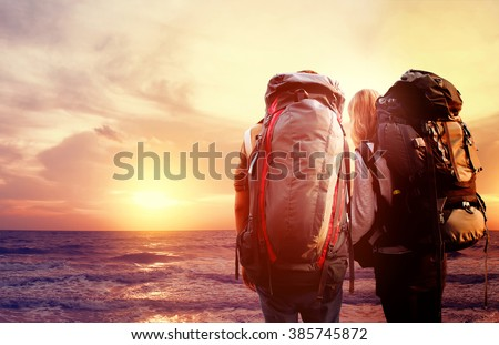 traveler with backpack walking over bridge and sunlight with sea sunset background [Blur and Select focus background]