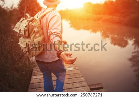 traveler with backpack walking over wooden bridge on the lake in sunset