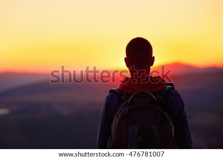 Traveler with backpack watching amazing sunset. Silhouette of the young man on the mountain top. Krkonose mountains, Czech Republic - Shutterstock ID 476781007
