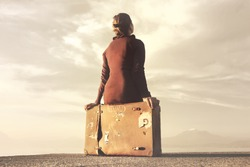 Traveler woman arriving at destination relaxes sitting on her suitcase