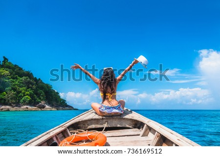 Traveler woman in bikini relaxing and enjoying on wooden boat her arms open feeling freedom, Andaman sea, Mu Koh Surin National Park, Phangnga, Travel in Thailand, Summer holiday and vacation trip
