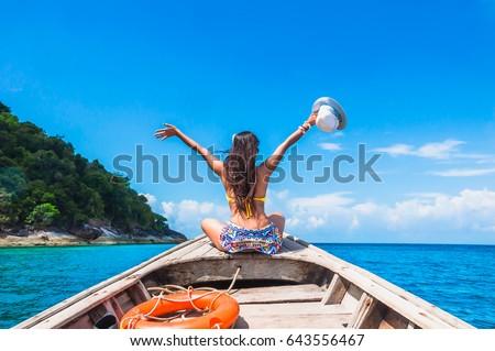 Shutterstock Traveler woman in bikini relaxing on wooden boat her arms open feeling freedom, Andaman sea, Mu Koh Surin national park, Phangnga, Thailand