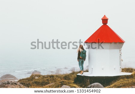 Traveler woman near lighthouse enjoying foggy sea view solo traveling lifestyle journey adventure outdoor solitude emotions #1331454902