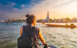 Traveler woman on boat joy view Wat Arun at sunset, Chao Phraya river, Famous water landmark travel Bangkok Thailand, tourist female on holiday vacation trips, Tourism beautiful destination place Asia