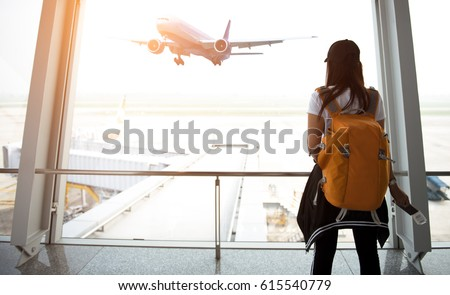 Traveler woman plan and backpack  see the airplane at the airport glass window, girl tourist hold bag and waiting near luggage in hall airplane departure.  Travel Concept