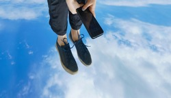 Traveler woman relaxing on nature (Smartphone photo).Woman lie above blue sky with clouds, view on the legs in casual shoes. Image made on mobile cell phone