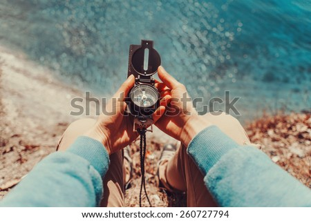 Traveler woman searching direction with a compass on coastline near the sea. Point of view shot