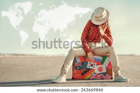Traveler woman sits on suitcase with stamps flags of different countries. Map of the world in sky. Concept of travel