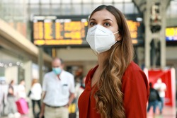 Traveler woman wearing KN95 FFP2 face mask at the airport. Young caucasian woman with behind timetables of departures arrivals waiting worried information for her flight.