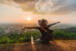 Traveler woman with backpack joy relaxing on hill top at sunset time her arms open felling freedom, Outdoor activity, Hatyai viewpoint, SongKhla, Travel nature Thailand, Summer holiday vacation trip
